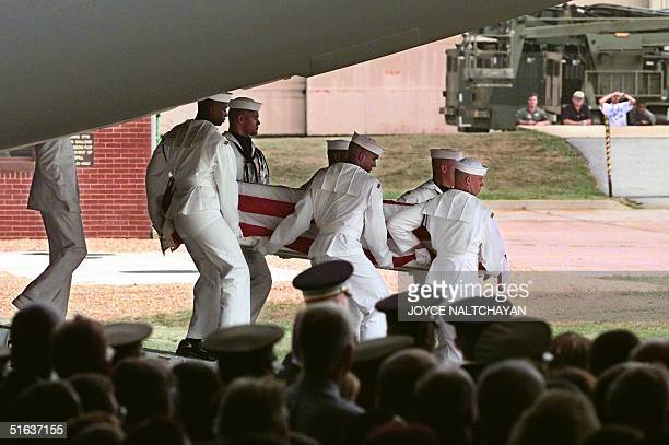 Honor guards carry a coffin off a military plane 13 August at Andrews Air Force Base MD prior to a memorial ceremony for 10 victims who lost their...