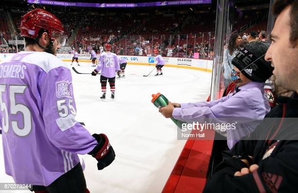 Honorary captain seven year old Bruce ClarkFrye who is battling leukenia sprays Jason Demers of the Arizona Coyotes with water before the start of a...