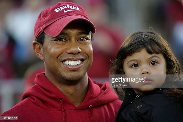 Honorary Standford Cardinal captain Tiger Woods holds his daugher Sam on the sidelines before the Cardinal game against the California Bears at...