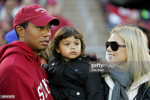 Honorary Standford Cardinal captain Tiger Woods holds his daugher Sam and speaks to his wife Elin Nordegren on the sidelines before the Cardinal game...