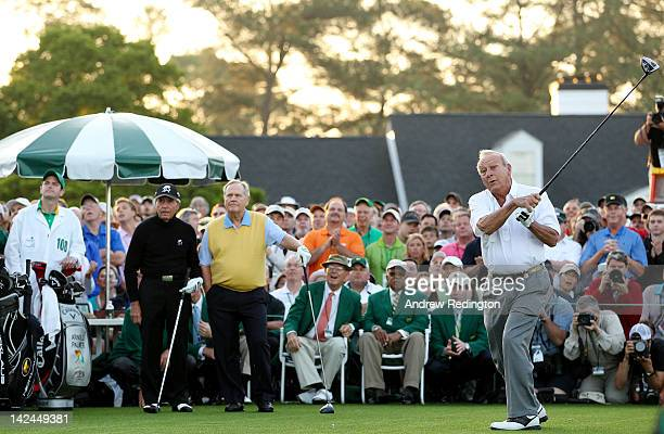 Honorary starter Arnold Palmer hits a tee shot as Gary Player of South Africa and Jack Nicklaus stand on the tee box at the start of the first round...