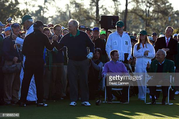 Honorary starters Jack Nicklaus and Gary Player shake hands and Arnold Palmer looks on during the ceremonial tee off to start the first round of the...