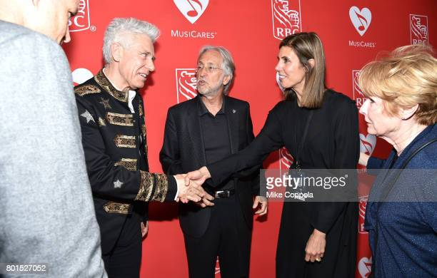 Honoree Adam Clayton of U2 greets Board Member Alexandra Patsavas as President/CEO of The Recording Academy and MusicCares Neil Portnow looks on at...