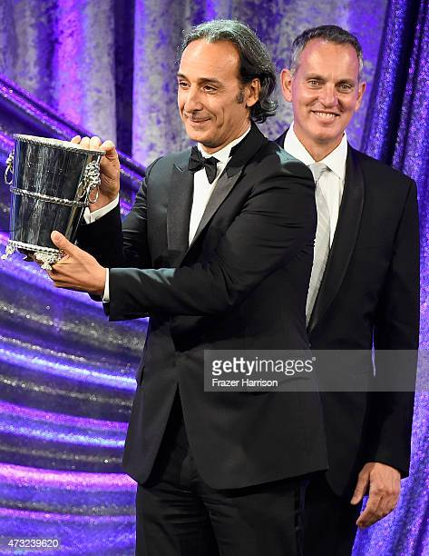 Honoree Alexandre Desplat accepts the BMI Icon Award from BMI president and CEO Mike O'Neil during the 2015 BMI Film Television Awards at the Beverly...
