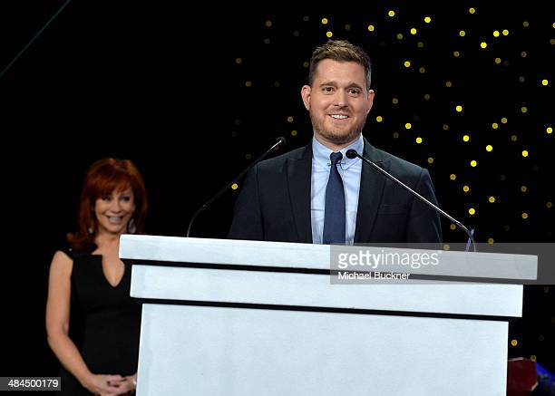 Honoree and singer Michael Buble accepts an award onstage with Emcee Reba McEntire during Muhammad Ali's Celebrity Fight Night XX held at the JW...