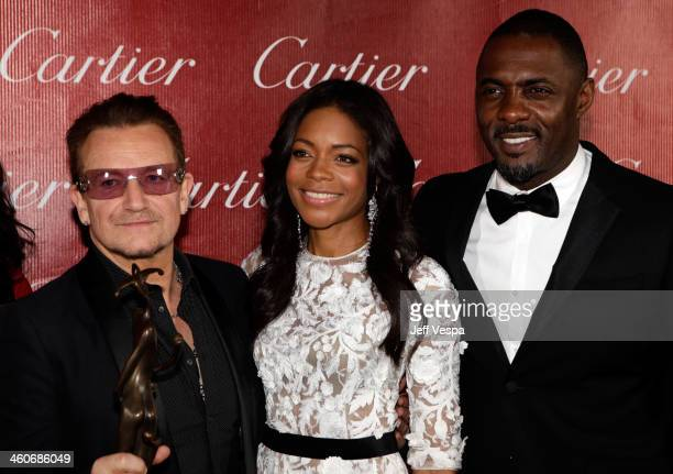 Honoree Bono presenters Naomie Harris and Idris Elba pose with the Sonny Bono Visionary Award backstage during the 25th annual Palm Springs...