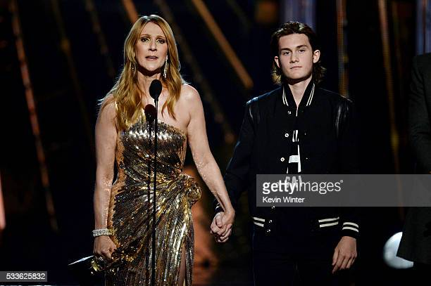 Honoree Celine Dion accepts the Billboard IconAward from son Rene Charles Angelil onstage during the 2016 Billboard Music Awards at TMobile Arena on...