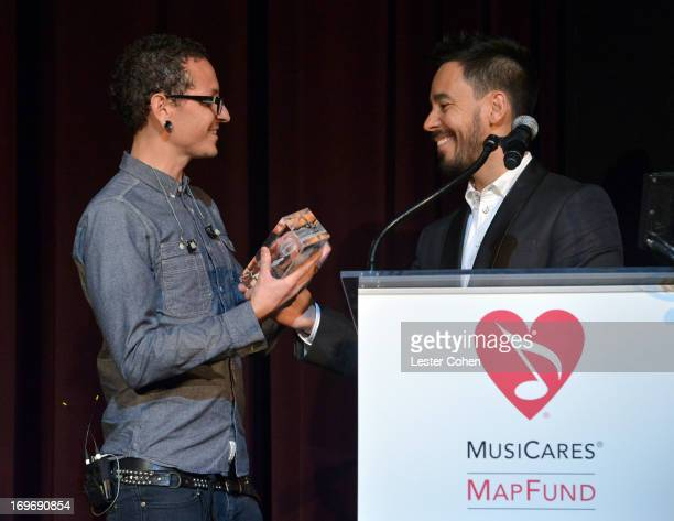 Honoree Chester Bennington receives his award from bandmate Mike Shinoda at the 2013 MusiCares MAP Fund Benefit Concert honoring Chester Bennington...
