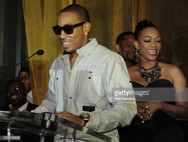 Honoree Chris Ludacris Bridges accepts The Make Change Award as Rapper Trina watches during Magnum Live Large Project VIP Party at Ventanas on June...