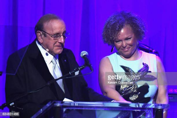 Honoree Debra Lee accepts the Icon Award from Clive Davis onstage at the PreGRAMMY Gala and Salute to Industry Icons Honoring Debra Lee at The...