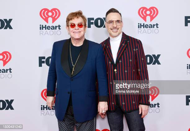 Honoree Elton John and David Furnish attend the 2021 iHeartRadio Music Awards at The Dolby Theatre in Los Angeles, California, which was broadcast...