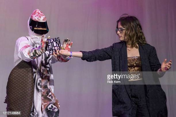 Honoree Erykah Badu accepts an award from host Parker Posey at the Austin Film Society's Texas Film Awards 20th Anniversary at Austin Studios on...