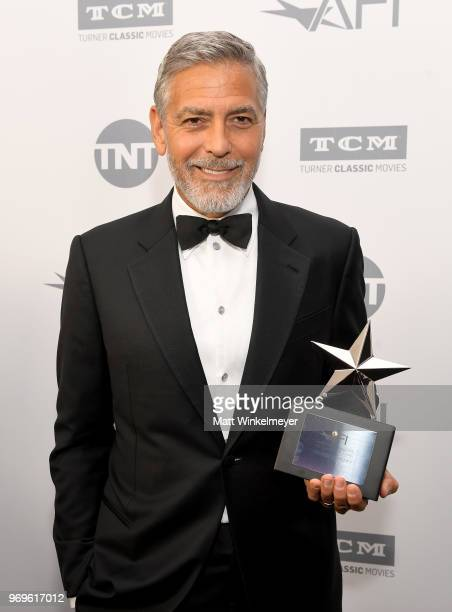 Honoree George Clooney poses with the Life Achievement trophy during the American Film Institute's 46th Life Achievement Award Gala Tribute to George...