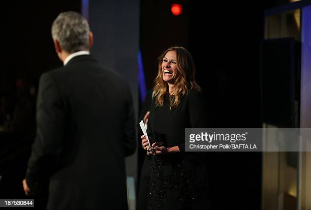Honoree George Clooney recipient of the Stanley Kubrick Britannia Award for Excellence in Film accepts his award from actress Julia Roberts onstage...