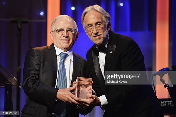 Honoree Irving Azoff accepts the President's Merit Award onstage from National Academy of Recording Arts and Sciences President Neil Portnow during...