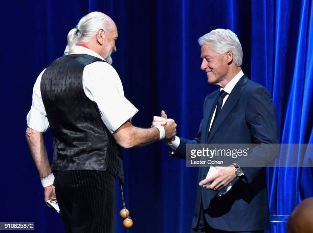 Honoree Mick Fleetwood of music group Fleetwood Mac accepts the MusiCares Person of the Year award from former President Bill Clinton onstage during...