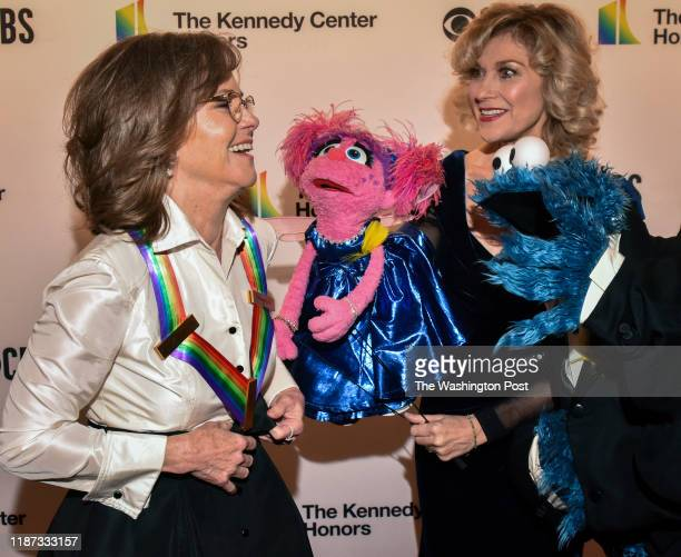 Honoree Sally Field is greeted by cohonorees Abby Cadabby and Cookie Monster as they arrive on the red carpet for the 42nd annual Kennedy Center...