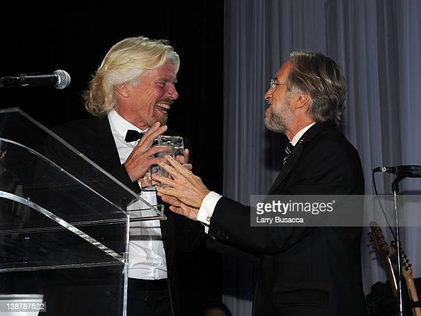 Honoree Sir Richard Branson accepts the Recording Academy Presidents Merit Award from President/CEO Recording Academy Neil Portnow onstage at Clive...