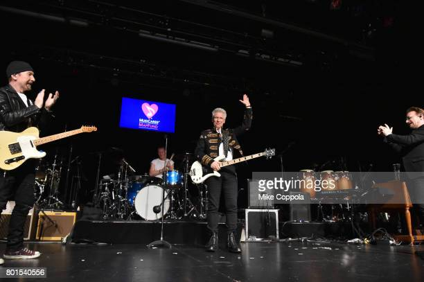 Honoree Stevie Ray Vaughan Award recipient Adam Clayton of U2 is congratulated by the band at the 13th Annual MusiCares MAP Fund Benefit Concert at...