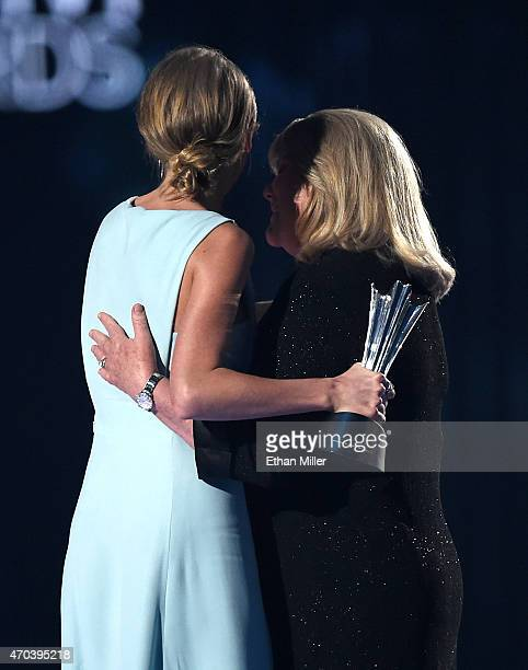Honoree Taylor Swift accepts the 50th Anniversary Milestone Award for Youngest ACM Entertainer of the Year from her mother Andrea Finlay onstage...