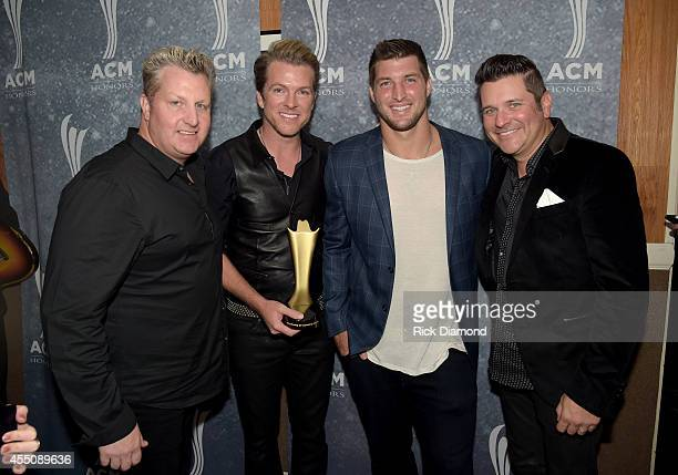 Honorees Gary LeVox Joe Don Rooney and Jay DeMarcus of Rascal Flatts pose with Tim Tebow backstage at the 8th Annual ACM Honors at Ryman Auditorium...