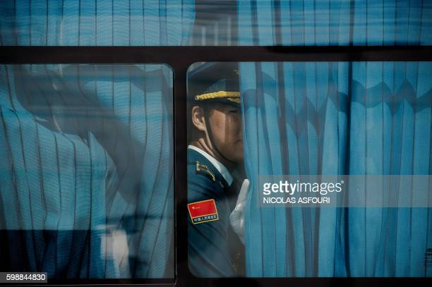 TOPSHOT A honour guard looks out from a bus ahead of US President Barack Obama arrival at Hangzhou Xiaoshan International Airport in Hangzhou on...
