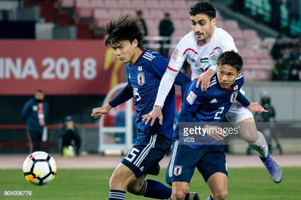 Honoya Shoji and So Fujitani of Japan and Yousef AlAshhab of Palestine compete for the ball during the AFC U23 Championship Group B match between...