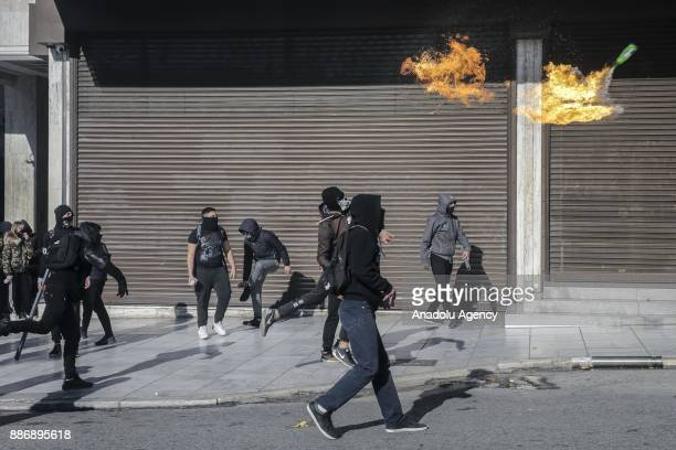 Hooded and masked youth throw molotov cocktail to police officers during a demonstration in central Athens on December 6 2017 commemorating the...
