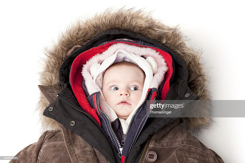 Hooded baby. Little girl in many winter jackets. : Stock Photo