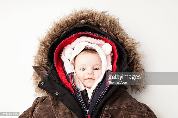hooded baby. little girl in many winter jackets. - warm clothing stock pictures, royalty-free photos & images