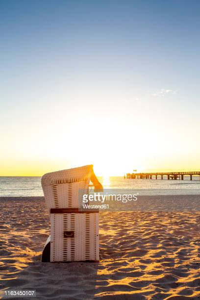 hooded beach chair at the beach against evening sun, heiligendamm, germany - heiligendamm stock photos and pictures