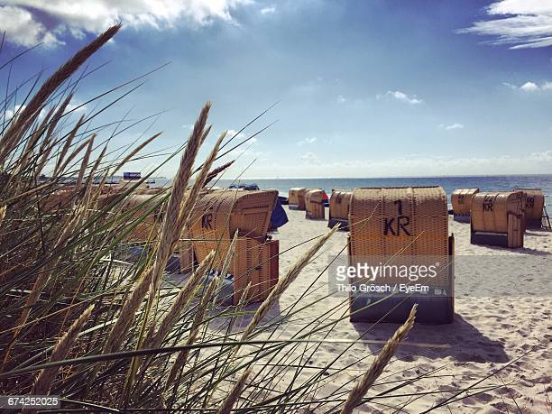 hooded beach chairs on sand against sky - fehmarn stock-fotos und bilder
