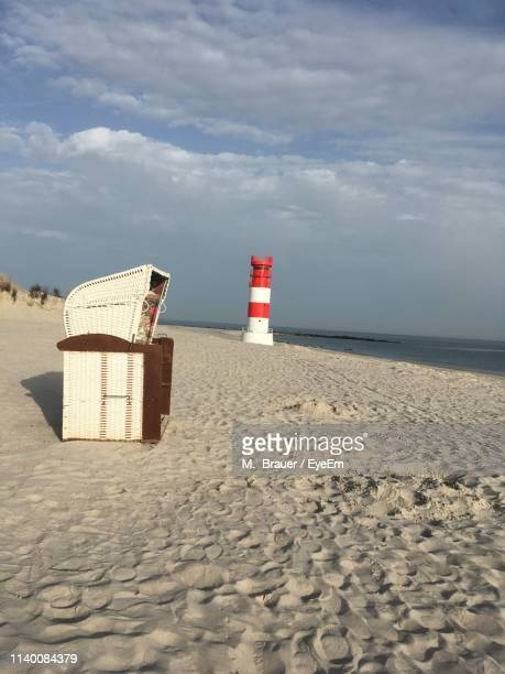 hooded beach chairs on sand at beach against cloudy sky - helgoland stock pictures, royalty-free photos & images