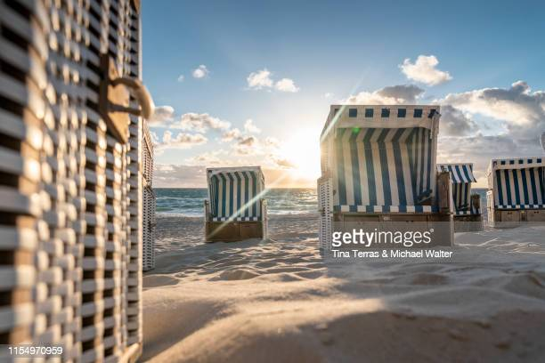 hooded beach chairs (strandkörbe) on the beach. - north sea stock pictures, royalty-free photos & images