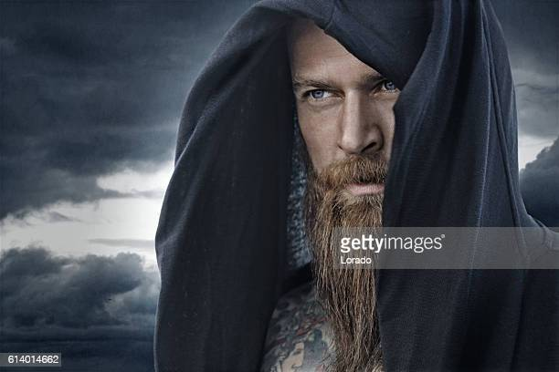 Hooded bearded tattooed male in fantasy cloudy seascape setting