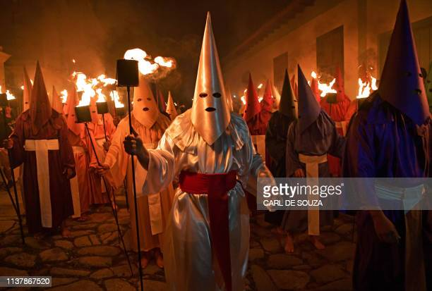 TOPSHOT Hooded catholic faithful representing Roman soldiers known as Farricocos carry flaming torches during the annual Fogareu Holy Week procession...