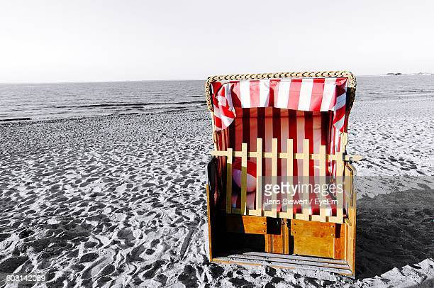 Hooded Chair On Sandy Beach Against Sky