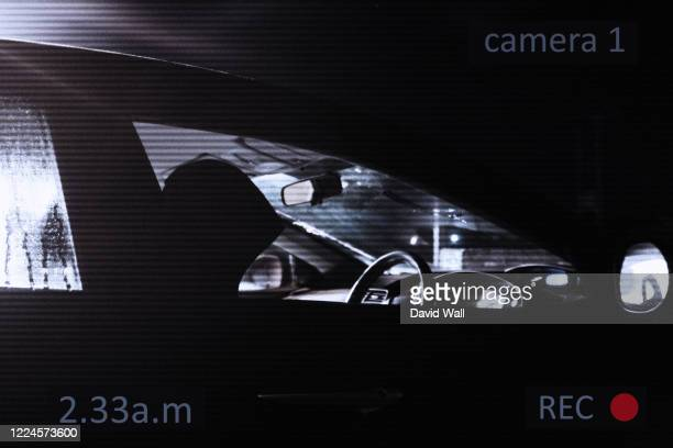 a hooded driver sitting in a car parked on the side of the road, underneath a street light, on a winters night. with a cctv surveillance edit. - crime stock pictures, royalty-free photos & images