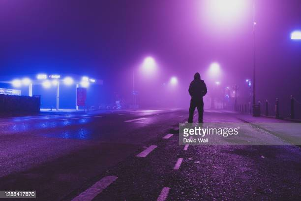 a hooded figure back to camera standing on a empty road in a city on a foggy, winters night. worcester, uk - night stock pictures, royalty-free photos & images