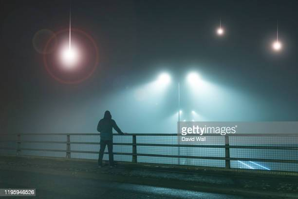 a hooded figure, standing with back to camera on a bridge, looking at ufo alien spaceships coming downfrom the sk., street lights. on a foggy night. - ufo stock pictures, royalty-free photos & images