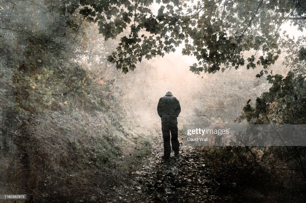 A hooded figure walking away from the camera on a misty woodland path with shoulders hunched and looking down. With a grunge, vintage edit : Stock Photo