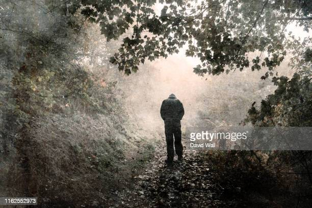a hooded figure walking away from the camera on a misty woodland path with shoulders hunched and looking down. with a grunge, vintage edit - suicidio fotografías e imágenes de stock