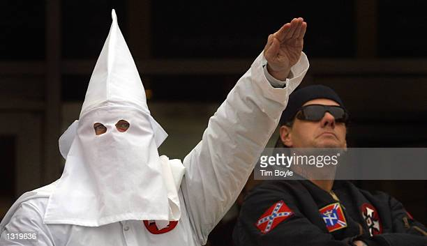 A hooded Klansman raises his left arm while another looks into the crowd during a Ku Klux Klan rally December 16 2000 in Skokie IL A Wisconsin...