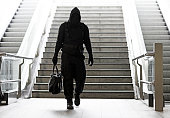 Hooded Lone wolf Man wearing black carrying bag in urban underground public transport setting