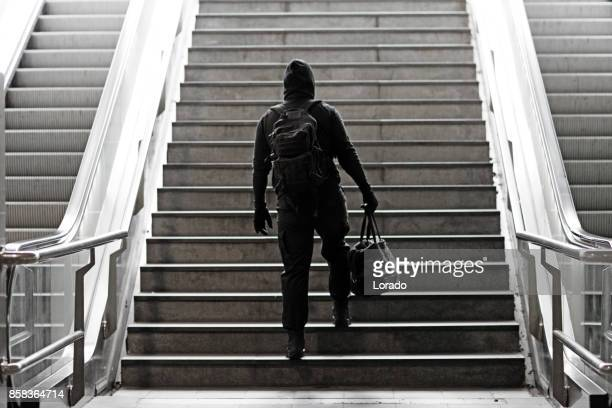 hooded lone wolf man wearing black carrying bag in urban underground public transport setting - terrorism stock pictures, royalty-free photos & images