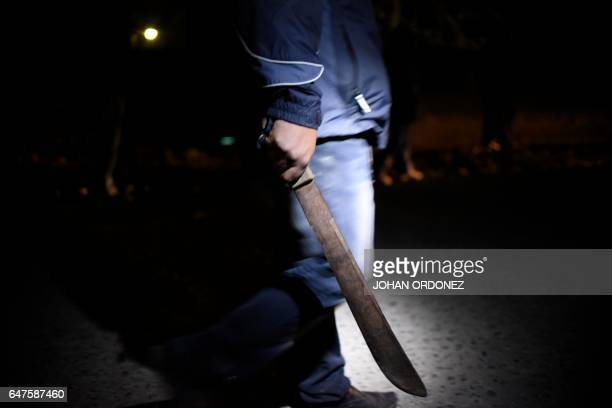 A hooded man carrying a machete patrols the streets in the village of 'Lo de Reyes' in the municipality of San Pedro Ayampuc 20 km north of Guatemala...