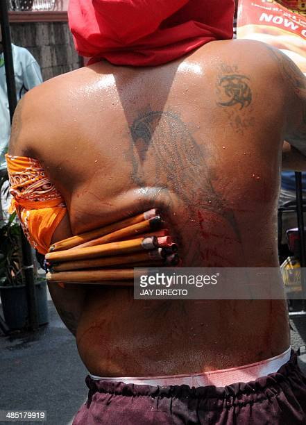 A hooded man flagellates himslef as part of popular rituals in penance for sins during Holy Thursday in Manila on April 17 Asia's bastion of...