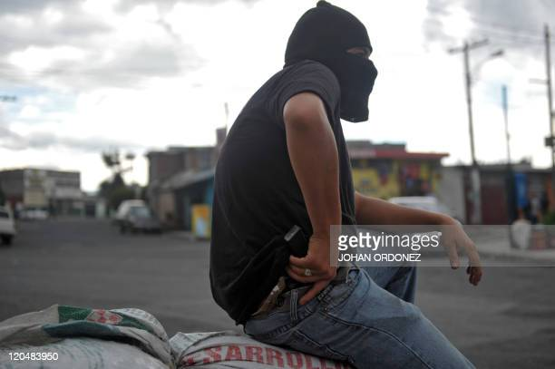 A hooded man holding a gun stands guard in the entrance of the Castanas neighborhood in the southern outskirts of Guatemala City on July 19 to...