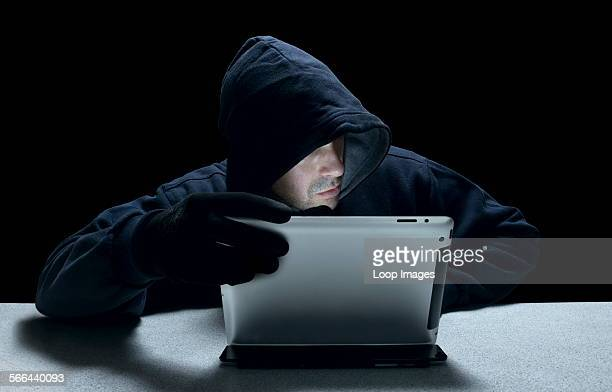 A hooded man representing a cyber criminal