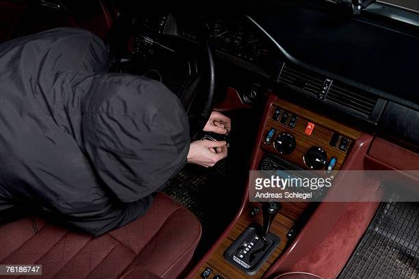 A hooded man starting a car with ignition circuit wires